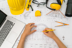 Hand over Construction plans with yellow helmet and drawing tool Royalty Free Stock Image