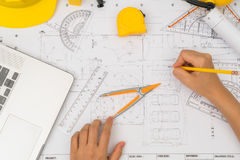 Hand over Construction plans with yellow helmet and drawing tool Royalty Free Stock Photography