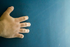 Hand over a gradient, dark blue surface. Hand over a gradient, dark blue degradated surface Royalty Free Stock Photos