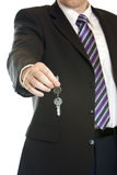 Hand-over of keys by business man. One businessman offers keys for handing over it. Isolated on white Royalty Free Stock Image