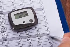 Hand Over Sheet With Digital Pedometer Royalty Free Stock Photography