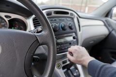 Hand på bilkugghjulförskjutning, med sikt av den klimatstyrning och instrumentbrädan royaltyfria bilder