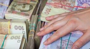 Hand på buntar av pengar Arkivfoto