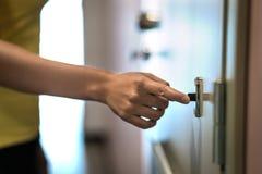 Hand på dörrklocka Finger som ringer ringklockan royaltyfri foto