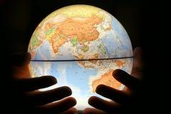 Hand på det ljusa jordklotet arkivbild