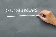 Hand på en svart tavla med det tyska ordet Deutschkurs (tysk Co Royaltyfri Foto