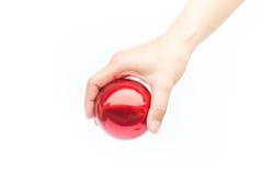 Hand på skinande röd boll på vit bakgrund Royaltyfria Foton