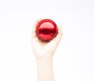 Hand på skinande röd boll på vit bakgrund Royaltyfri Foto
