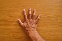 Hand på trät Hand på tabellen Arkivbilder