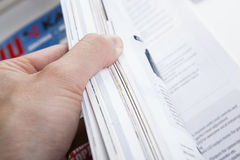 The hand through the pages of the magazine Royalty Free Stock Photo