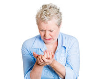 Hand pain. Closeup portrait, elderly, senior corporate employee, old woman looking miserable in great excruciating hand pain ache, isolated white background royalty free stock photo