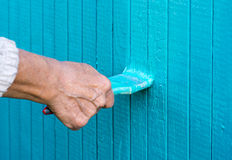 Hand with a paint brush paints wooden wall Stock Images