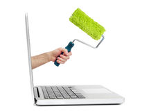 Hand with paint roller out of laptop Stock Photography