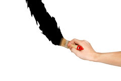 Hand with paintbrush black line painting. Isolated on white back Stock Photos