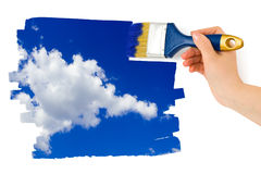 Hand with paintbrush painting sky Royalty Free Stock Photos