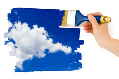 Hand with paintbrush painting sky Stock Image