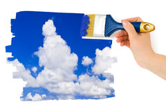 Hand with paintbrush painting sky Stock Images