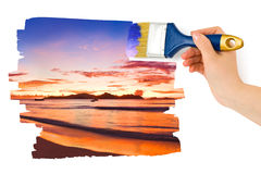 Hand with paintbrush painting sunset Royalty Free Stock Images