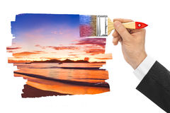 Hand with paintbrush painting sunset Stock Photo