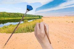 Hand with paintbrush paints river in sand desert Royalty Free Stock Photography