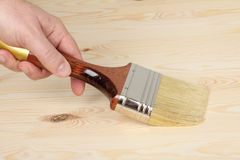 Hand with paintbrush on wood Stock Image