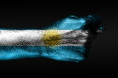 A hand with a painted Argentina flag shows a fig, a sign of aggression, disagreement, a dispute on a dark background. Horizontal frame royalty free stock photos