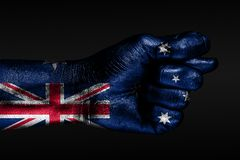 A hand with a painted Australia flag shows a fig, a sign of aggression, disagreement, a dispute on a dark background. Horizontal frame stock photos