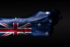 A hand with a painted Australia flag shows a fig, a sign of aggression, disagreement, a dispute on a dark background. Horizontal frame royalty free stock photo