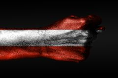A hand with a painted Austria flag shows a fig, a sign of aggression, disagreement, a dispute on a dark background. Horizontal frame stock image
