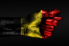 A hand with a painted Belgium flag shows a fig, a sign of aggression, disagreement, a dispute on a dark background. Horizontal frame royalty free stock photo