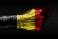A hand with a painted Belgium flag shows a fig, a sign of aggression, disagreement, a dispute on a dark background. Horizontal frame royalty free stock photography
