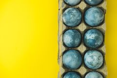 Hand painted blue Easter eggs in wreath on bright yellow background. The concept of spring holiday of Easter. Hand painted blue Easter eggs in wreath on bright stock photography