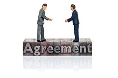 Agreement word in letterpress with miniature businessmen Royalty Free Stock Photos