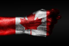 A hand with a painted Canada flag shows a fig, a sign of aggression, disagreement, a dispute on a dark background. Horizontal frame stock photo