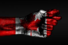 A hand with a painted Canada flag shows a fig, a sign of aggression, disagreement, a dispute on a dark background. Horizontal frame stock image