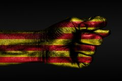 A hand with a painted Catalonia flag shows a fig, a sign of aggression, disagreement, a dispute on a dark background. Horizontal frame royalty free stock photo