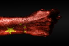 A hand with a painted China flag shows a fig, a sign of aggression, disagreement, a dispute on a dark background. Horizontal frame royalty free stock images