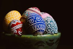 Hand-painted colorful eggs in a hand-crafted ceramic bowl on the dark background stock photography