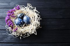 Hand painted dark blue easter eggs in nest and flowers. On wooden table stock image
