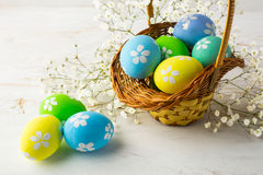 Hand-painted decorated Easter eggs in the basket. With small white baby's breath flowers on a white wooden background, close up Royalty Free Stock Photography