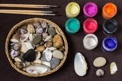 Hand-painted dot patterns on sea pebbles and shells. Step 1. Hand-painted colorful dot patterns on sea pebbles and shells. Children`s art project, a craft for stock photos