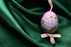 Hand painted easter egg. With ribbon on creased green satin fabric background Stock Photography