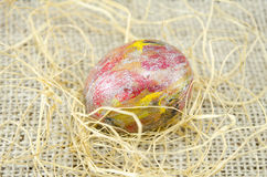 Hand painted Easter egg and straws Stock Photo