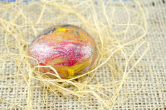 Hand painted Easter egg and straws Stock Photos
