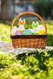 Hand painted Easter eggs and bunny in big rattan basket on green grass on white towel. Traditional decoration for Easter stock image