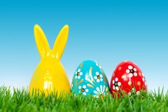 Hand painted Easter eggs and bunny rabbit toy on grass Stock Images