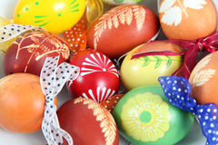 Easter eggs. Hand painted Easter eggs with ribbons on a white plate stock photography