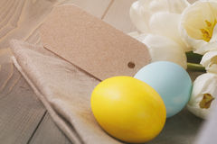 Hand painted easter eggs on table with tulips Royalty Free Stock Photo