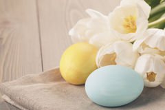 Hand painted easter eggs on table with tulips Stock Image