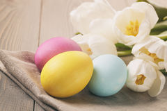 Hand painted easter eggs on table with tulips Stock Photos